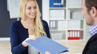 Woman in a job interview handing over CV
